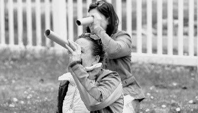 two women looking through cardboard tubes