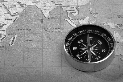 navigational compass sitting on a map of southern asia