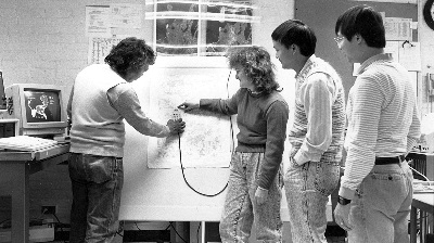 men and women standing around a computerized easel in the 1980s