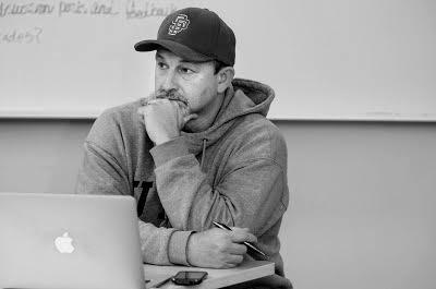 man in a baseball cap listening in class