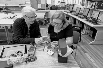 older man and woman working with a multimeter