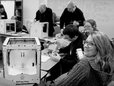 Woman smiling at the camera while sitting next to a 3D printer