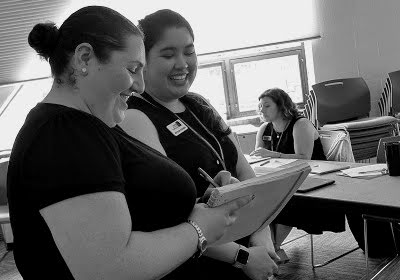 female instructor and student smiling while one is writing