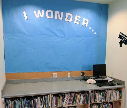 "Blue paper with the words ""I Wonder"" written in all caps. Letters are cut out of white paper and glued onto blue paper."
