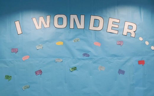 """Blue paper with words """"I wonder"""". About a dozen speech bubbles of different colors are stapled to blue paper."""