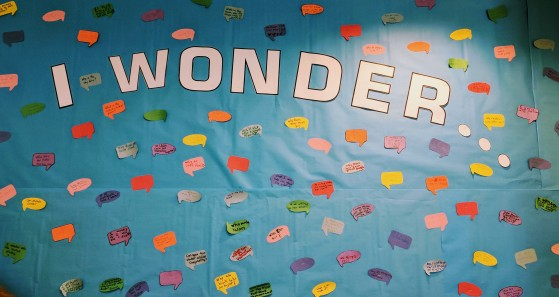 """Blue paper with white letters that say """"I wonder."""" Paper is covered in small speech bubbles."""